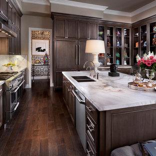 Große Klassische Wohnküche in U-Form mit Doppelwaschbecken, Glasfronten, dunklen Holzschränken, Küchenrückwand in Weiß, Küchengeräten aus Edelstahl, dunklem Holzboden, Marmor-Arbeitsplatte, Rückwand aus Stein, Kücheninsel und braunem Boden in Las Vegas