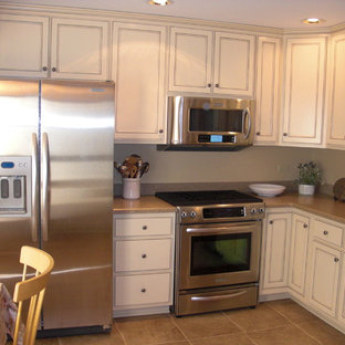 This is an example of a small traditional l-shaped eat-in kitchen in Chicago with an undermount sink, recessed-panel cabinets, white cabinets, granite benchtops, stainless steel appliances, ceramic floors and no island.