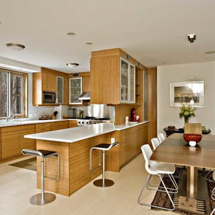 This is an example of a mid-sized modern galley eat-in kitchen in New York with a drop-in sink, flat-panel cabinets, light wood cabinets, quartzite benchtops, white splashback, subway tile splashback, stainless steel appliances, vinyl floors, a peninsula and beige floor.