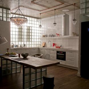 Offene Industrial Küche mit weißen Schränken, Arbeitsplatte aus Fliesen, Küchenrückwand in Weiß, schwarzen Elektrogeräten und dunklem Holzboden in Moskau