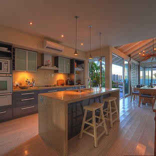 Tropical kitchen photos - Inspiration for a tropical galley bamboo floor kitchen remodel in Cairns with concrete countertops and an island