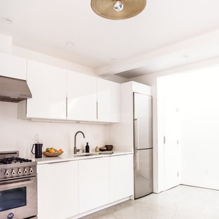 Mid-sized modern eat-in kitchen designs - Example of a mid-sized minimalist single-wall concrete floor eat-in kitchen design in San Francisco with a double-bowl sink, flat-panel cabinets, white cabinets, solid surface countertops, white backsplash, stainless steel appliances and no island
