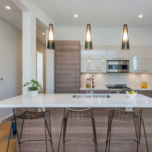 Contemporary kitchen pictures - Example of a trendy galley light wood floor kitchen design in San Francisco with an undermount sink, flat-panel cabinets, medium tone wood cabinets, gray backsplash, glass sheet backsplash, stainless steel appliances and an island