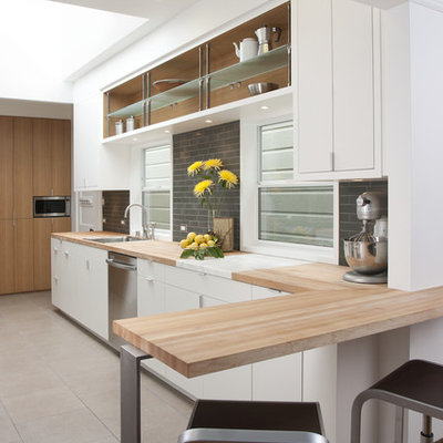 Example of a minimalist kitchen design in San Francisco with flat-panel cabinets, stainless steel appliances, wood countertops, white cabinets, gray backsplash and subway tile backsplash