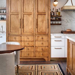 Inredning av ett klassiskt stort kök, med en rustik diskho, släta luckor, vita skåp, marmorbänkskiva, vitt stänkskydd, stänkskydd i marmor, rostfria vitvaror, mellanmörkt trägolv, en köksö och brunt golv