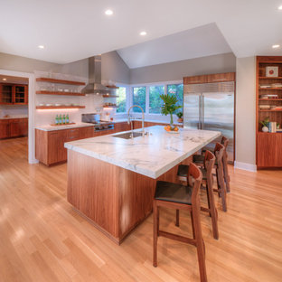 Large contemporary eat-in kitchen appliance - Large trendy l-shaped light wood floor and orange floor eat-in kitchen photo in San Diego with flat-panel cabinets, medium tone wood cabinets, marble countertops, white backsplash, subway tile backsplash, stainless steel appliances, an island, white countertops and an undermount sink