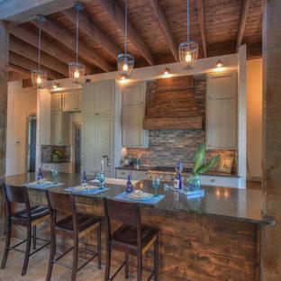 オースティンの小さいラスティックスタイルのおしゃれなキッチン (エプロンフロントシンク、シェーカースタイル扉のキャビネット、グレーのキャビネット、御影石カウンター、マルチカラーのキッチンパネル、レンガのキッチンパネル、シルバーの調理設備、コンクリートの床) の写真