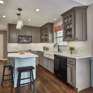 ダラスの小さいシャビーシック調のおしゃれなキッチン (エプロンフロントシンク、シェーカースタイル扉のキャビネット、グレーのキャビネット、クオーツストーンカウンター、白いキッチンパネル、セラミックタイルのキッチンパネル、黒い調理設備、無垢フローリング、茶色い床、白いキッチンカウンター) の写真