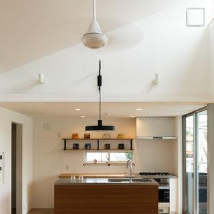 東京23区のモダンスタイルのおしゃれなキッチン (シングルシンク、ステンレスカウンター、白いキッチンパネル、無垢フローリング、茶色い床) の写真