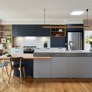 Design ideas for a contemporary kitchen in Melbourne with flat-panel cabinets, white splashback, stainless steel appliances, light hardwood floors, with island, beige floor and white benchtop.