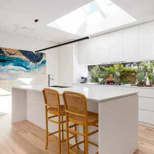 Inspiration for a mid-sized contemporary galley open plan kitchen in Melbourne with an undermount sink, flat-panel cabinets, white cabinets, quartz benchtops, window splashback, stainless steel appliances, light hardwood floors, with island, beige floor and white benchtop.