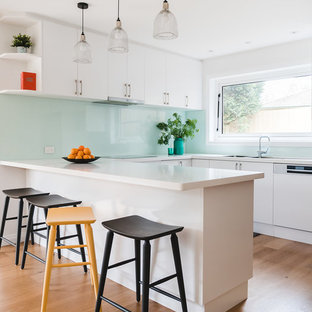 This is an example of a large contemporary u-shaped open plan kitchen in Melbourne with a double-bowl sink, flat-panel cabinets, white cabinets, granite benchtops, green splashback, glass sheet splashback, brown floor, white benchtop, panelled appliances, medium hardwood floors and a peninsula.