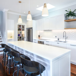 Design ideas for a large transitional galley open plan kitchen in Sydney with an undermount sink, shaker cabinets, white cabinets, solid surface benchtops, beige splashback, porcelain splashback, stainless steel appliances, dark hardwood floors, with island, brown floor and white benchtop.