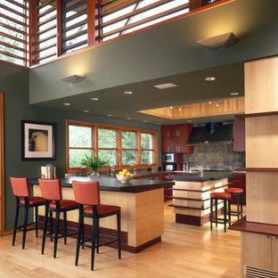 デンバーの大きいラスティックスタイルのおしゃれなキッチン (スレートの床、アンダーカウンターシンク、フラットパネル扉のキャビネット、赤いキャビネット、ソープストーンカウンター、グレーのキッチンパネル、淡色無垢フローリング、黒いキッチンカウンター) の写真