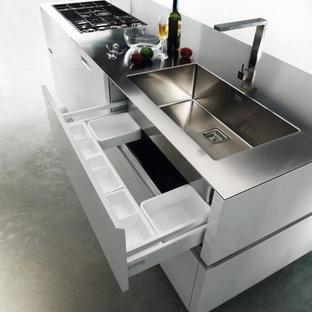 Imagen de cocina de galera, moderna, pequeña, abierta, con armarios con paneles lisos, electrodomésticos de acero inoxidable, suelo de cemento y una isla