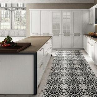 サンフランシスコの大きいシャビーシック調のおしゃれなキッチン (アンダーカウンターシンク、落し込みパネル扉のキャビネット、白いキャビネット、クオーツストーンカウンター、ベージュキッチンパネル、石スラブのキッチンパネル、シルバーの調理設備の、セラミックタイルの床、白い床、ベージュのキッチンカウンター) の写真