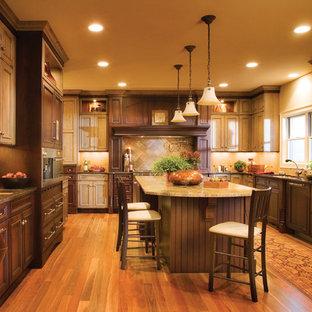 ミネアポリスの大きいエクレクティックスタイルのおしゃれなキッチン (アンダーカウンターシンク、フラットパネル扉のキャビネット、ヴィンテージ仕上げキャビネット、御影石カウンター、茶色いキッチンパネル、シルバーの調理設備の、無垢フローリング) の写真
