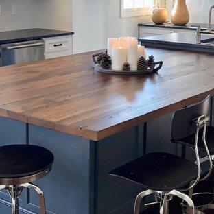 他の地域の大きいカントリー風おしゃれなキッチン (エプロンフロントシンク、フラットパネル扉のキャビネット、グレーのキャビネット、木材カウンター、白いキッチンパネル、大理石のキッチンパネル、シルバーの調理設備、無垢フローリング、茶色い床、茶色いキッチンカウンター) の写真