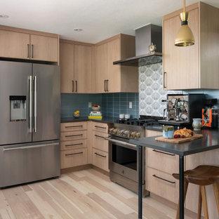 Geschlossene Eklektische Küche in U-Form mit hellen Holzschränken, Quarzwerkstein-Arbeitsplatte, Küchenrückwand in Blau, Rückwand aus Glasfliesen, Küchengeräten aus Edelstahl, hellem Holzboden und schwarzer Arbeitsplatte in Denver