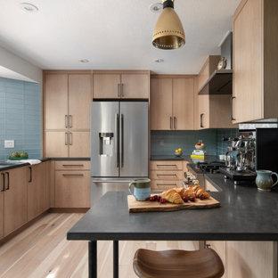 Geschlossene Moderne Küche in U-Form mit Unterbauwaschbecken, hellen Holzschränken, Quarzwerkstein-Arbeitsplatte, Küchenrückwand in Blau, Rückwand aus Glasfliesen, Küchengeräten aus Edelstahl, hellem Holzboden und schwarzer Arbeitsplatte in Denver