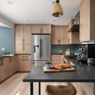 Trendy u-shaped light wood floor enclosed kitchen photo in Denver with an undermount sink, light wood cabinets, quartz countertops, blue backsplash, glass tile backsplash, stainless steel appliances and black countertops