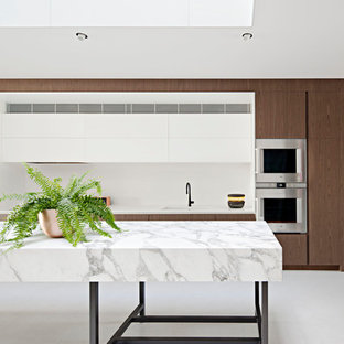 Photo of a contemporary galley kitchen in Melbourne with flat-panel cabinets, dark wood cabinets, stainless steel appliances, with island, grey floor and white benchtop.