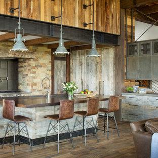Diseño de cocina rústica, abierta, con salpicadero marrón, electrodomésticos de acero inoxidable, suelo de madera en tonos medios, una isla, suelo marrón y encimeras marrones