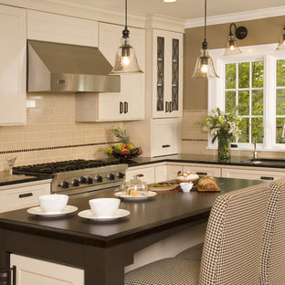 Traditional kitchen ideas - Elegant kitchen photo in Seattle with recessed-panel cabinets, stainless steel appliances, white cabinets, wood countertops, beige backsplash, subway tile backsplash and an undermount sink