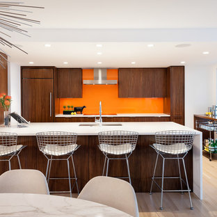 Contemporary eat-in kitchen ideas - Inspiration for a contemporary galley light wood floor and beige floor eat-in kitchen remodel in Seattle with an undermount sink, flat-panel cabinets, dark wood cabinets, orange backsplash, glass sheet backsplash, paneled appliances, a peninsula and white countertops