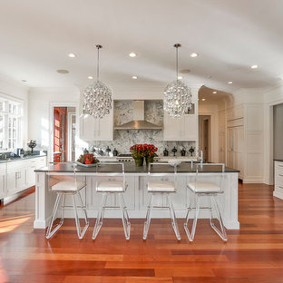Example of a huge transitional u-shaped dark wood floor open concept kitchen design in New York with an undermount sink, shaker cabinets, white cabinets, limestone countertops, gray backsplash, stone slab backsplash, stainless steel appliances and an island