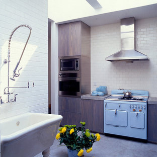 Photo of a mid-sized midcentury l-shaped separate kitchen in New York with a farmhouse sink, flat-panel cabinets, dark wood cabinets, granite benchtops, white splashback, subway tile splashback, coloured appliances and concrete floors.