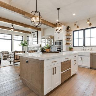Idee per una cucina abitabile country con ante lisce, paraspruzzi bianco, elettrodomestici in acciaio inossidabile, parquet chiaro, isola e top bianco