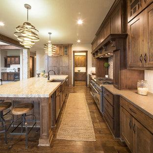 Urige Küche mit Landhausspüle, Schrankfronten im Shaker-Stil, dunklen Holzschränken, Küchenrückwand in Beige, Rückwand aus Metrofliesen, dunklem Holzboden und Kücheninsel in Dallas