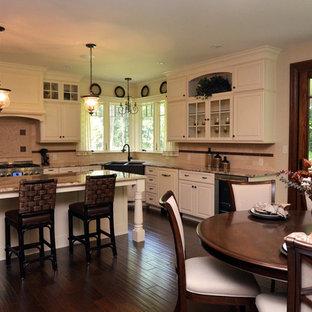 Klassische Wohnküche in L-Form mit Unterbauwaschbecken, profilierten Schrankfronten, gelben Schränken, Granit-Arbeitsplatte, Küchenrückwand in Beige, Rückwand aus Travertin, Küchengeräten aus Edelstahl, dunklem Holzboden, Kücheninsel und braunem Boden in New York