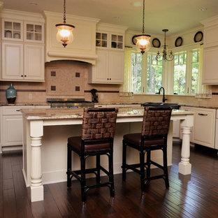 Klassische Wohnküche in L-Form mit Granit-Arbeitsplatte, Küchenrückwand in Beige, Küchengeräten aus Edelstahl, dunklem Holzboden, Kücheninsel, Unterbauwaschbecken, profilierten Schrankfronten, gelben Schränken, Rückwand aus Travertin und braunem Boden in New York