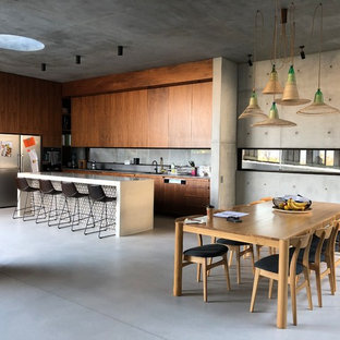Photo of an industrial l-shaped kitchen in Sydney with flat-panel cabinets, dark wood cabinets, stainless steel appliances, concrete floors, with island, grey floor and white benchtop.