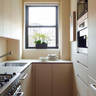 Diseño de cocina de galera, contemporánea, pequeña, con fregadero bajoencimera, armarios con paneles lisos, puertas de armario beige, electrodomésticos de acero inoxidable y salpicadero beige
