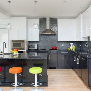 Mittelgroße Moderne Wohnküche in L-Form mit Unterbauwaschbecken, flächenbündigen Schrankfronten, Quarzwerkstein-Arbeitsplatte, Küchengeräten aus Edelstahl, hellem Holzboden, Kücheninsel, Küchenrückwand in Blau, Rückwand aus Glasfliesen und grauen Schränken in Chicago