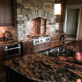他の地域の中サイズのラスティックスタイルのおしゃれなキッチン (シェーカースタイル扉のキャビネット、濃色木目調キャビネット、御影石カウンター、ベージュキッチンパネル、石タイルのキッチンパネル、パネルと同色の調理設備、無垢フローリング) の写真