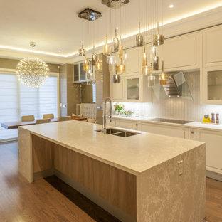 Idéer för att renovera ett stort funkis beige beige kök, med en undermonterad diskho, skåp i shakerstil, vita skåp, bänkskiva i kvartsit, beige stänkskydd, stänkskydd i stenkakel, vita vitvaror, mellanmörkt trägolv, en köksö och brunt golv