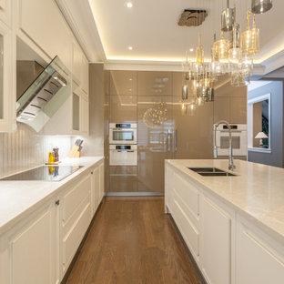 Große Moderne Wohnküche in L-Form mit Unterbauwaschbecken, Schrankfronten im Shaker-Stil, weißen Schränken, Quarzit-Arbeitsplatte, Küchenrückwand in Beige, Rückwand aus Steinfliesen, weißen Elektrogeräten, braunem Holzboden, Kücheninsel, braunem Boden, beiger Arbeitsplatte und eingelassener Decke in Toronto