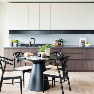 Inspiration for a contemporary l-shaped kitchen/diner in London with flat-panel cabinets, white cabinets, stainless steel appliances, light hardwood flooring, no island, beige floors and grey worktops.