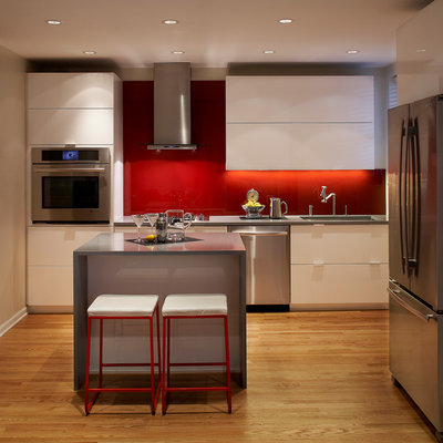Example of a minimalist kitchen design in Chicago with flat-panel cabinets, white cabinets, red backsplash and stainless steel appliances