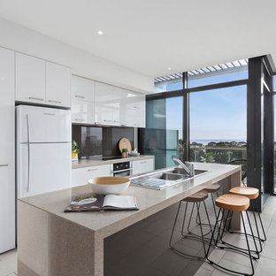 This is an example of a contemporary galley kitchen in Geelong with a double-bowl sink, flat-panel cabinets, white cabinets, black splashback, glass sheet splashback, stainless steel appliances, with island, beige floor and beige benchtop.