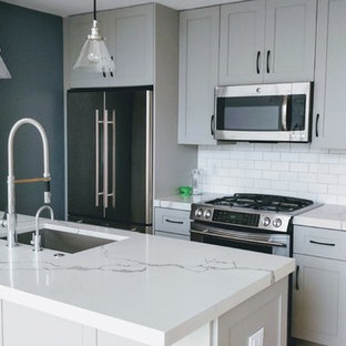 Small modern eat-in kitchen designs - Small minimalist galley light wood floor and brown floor eat-in kitchen photo in New York with an undermount sink, shaker cabinets, gray cabinets, quartz countertops, stainless steel appliances, white backsplash, subway tile backsplash, an island and white countertops