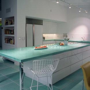 Пример оригинального дизайна: п-образная кухня среднего размера в современном стиле с обеденным столом, плоскими фасадами, белыми фасадами, столешницей из бетона, белым фартуком, белой техникой, островом и бирюзовой столешницей