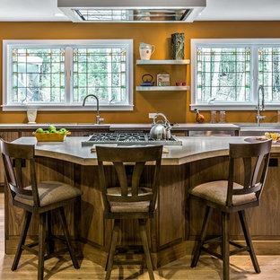 ポートランド(メイン)の中くらいのおしゃれなキッチン (エプロンフロントシンク、フラットパネル扉のキャビネット、中間色木目調キャビネット、ステンレスカウンター、オレンジのキッチンパネル、シルバーの調理設備、淡色無垢フローリング) の写真