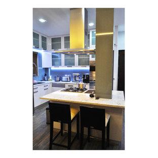 他の地域の大きいアジアンスタイルのおしゃれなキッチン (ダブルシンク、ガラス扉のキャビネット、白いキャビネット、御影石カウンター、グレーのキッチンパネル、ガラス板のキッチンパネル、シルバーの調理設備、磁器タイルの床) の写真