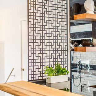 トロントの中サイズのアジアンスタイルのおしゃれなキッチン (アンダーカウンターシンク、フラットパネル扉のキャビネット、中間色木目調キャビネット、大理石カウンター、黒いキッチンパネル、大理石の床、シルバーの調理設備の、コンクリートの床、グレーの床) の写真