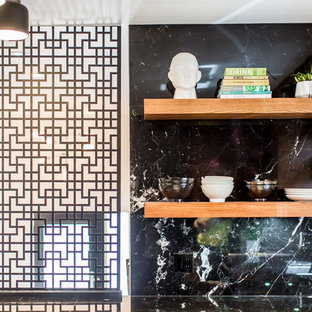 トロントの中くらいのアジアンスタイルのおしゃれなキッチン (アンダーカウンターシンク、フラットパネル扉のキャビネット、中間色木目調キャビネット、大理石カウンター、黒いキッチンパネル、大理石のキッチンパネル、シルバーの調理設備、コンクリートの床、グレーの床) の写真